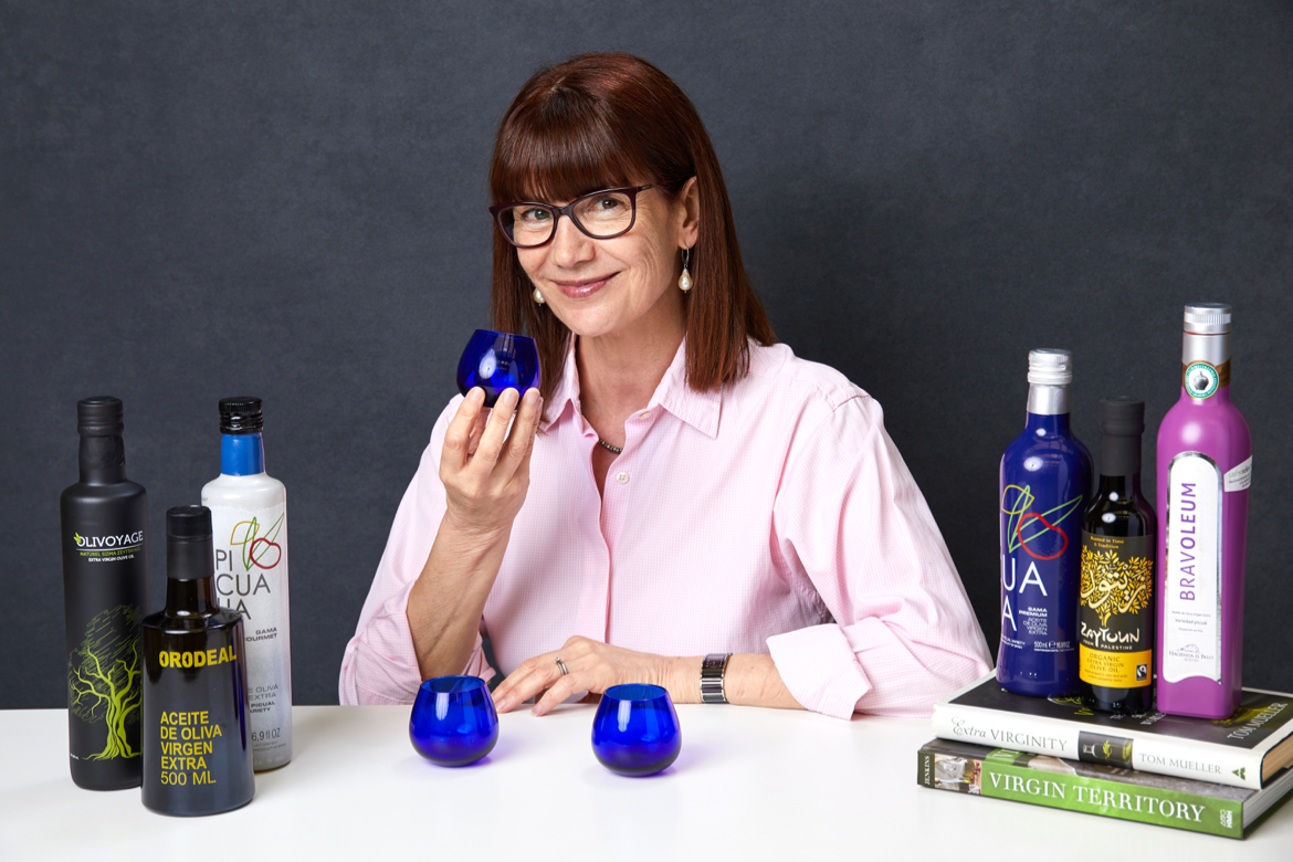 Photo of Karen Ormiston seated with a selection of olive oils