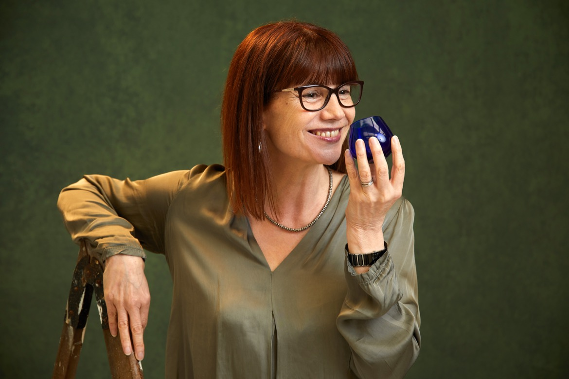 Photo of Karen O savouring the aroma of a sample of extra-virgin olive oil